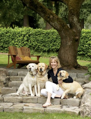 Liz Williams relaxes with beloved yellow Labrador Retrievers (left to right) Riley, Higgins, and Mimi. Behind them is the playfield used by the three Williams children, and it borders the expanding vegetable garden where Nick Williams relaxes after work.