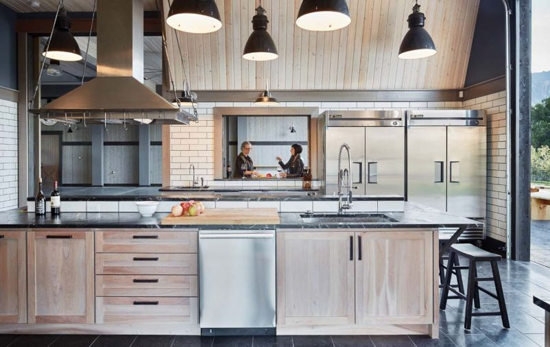 The commercial kitchen features industrial pendant lamps imported from Europe, a professional wood burning Mugnaini pizza oven, Perlick refrigerator drawers, wine and beverage coolers.