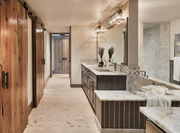 The master bathroom features rare quartz slab countertops, dark stained oak cabinets, with white glaze beadboard and hydronic heated floors.