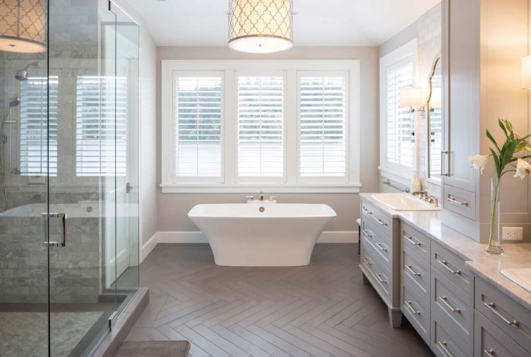 The herringbone motif from the dining room and breakfast nook is carried into the master bathroom, but here, it's found on the floor rather than the wall. Symmetrical design principles carry through even to the more functional components of the home, like the shower and storage areas.
