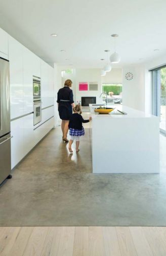 """The neutral monotone works really well with the surrounding cool concrete flooring in the kitchen and as a counterpoint to the warmer finishes and accents in the living and dining rooms,"" explains designer Cathleen Summers of Summers Studio."