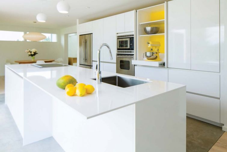 "Homeowner Michaela Spaeth wanted to see a ""happy"" yellow color inside the central cabinet, and SieMatic had just introduced a signature yellow lacquer accent color that matches her KitchenAid perfectly."