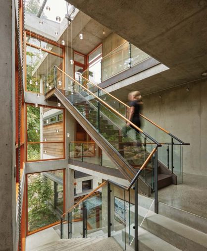 "Three stories of living space are linked with a steel and concrete staircase illuminated by a custom LED light fixture made from hand-cast glass globes. ""It's so beautiful at night,"" says McClellan. ""You can see the light fixture from the entry door, and it reflects in the windows and the glass railing so it appears there are about three times more lights than there really are."""