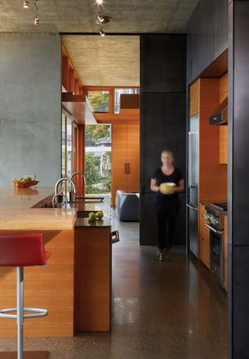 In the kitchen, the cabinetry is made from vertical grain fir, while the darker material around the perimeter of the cabinetry is blackened steel.
