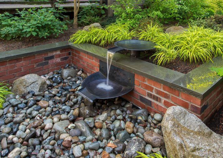 Water flows down the tiers of spun copper bowls and disappears in a cistern under pebbles where it recirculates back to the start of the sequence. A waterproof up light provides drama at night.