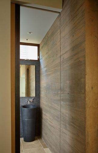 A concrete powder room wall plays off Stone Forest Veneto Sink and Mud Wood Chip Mosaic tile.