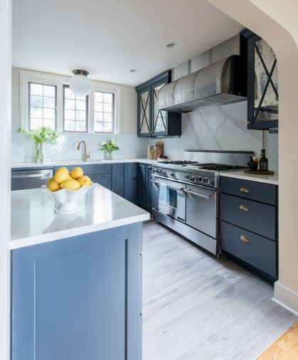 The combination of navy cabinetry with white countertops and tile gives a crisp, tailored look. Because the family cooks frequently, Heather opted for a durable quartz product for the countertops and oven backsplash, finished to resemble Calcutta marble.