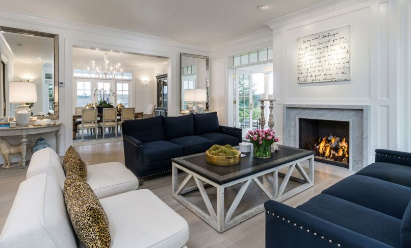 Navy blue sofas ground the light-filled formal living room that is walled by French doors.
