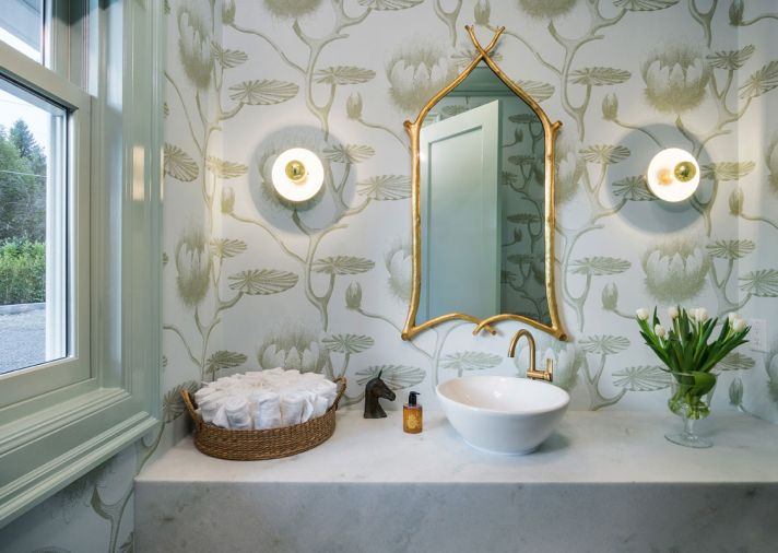 A powder room uses the same blue tones and brass accents as seen elsewhere but adds whimsy in the stylized lily wallpaper.
