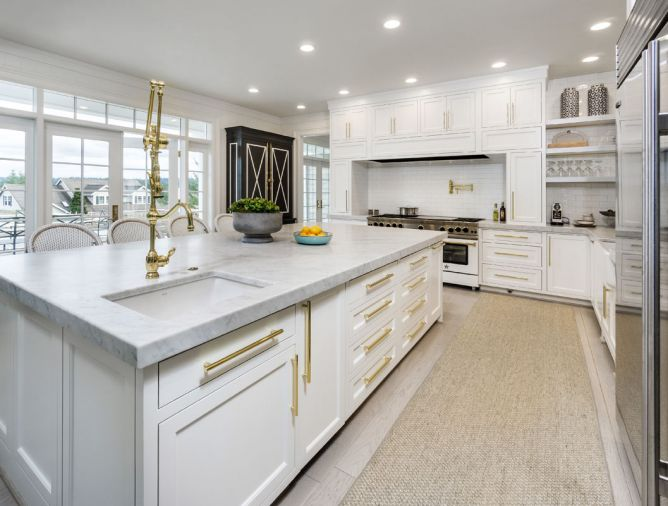 A Blue Star custom range from Eastbank Contractor Appliances takes center stage. Subway tile, Carrara marble, and classic cabinets combine with stainless steel appliances and brass hardware in a twist on tradition. A spacious island forms the kitchen's epicenter.