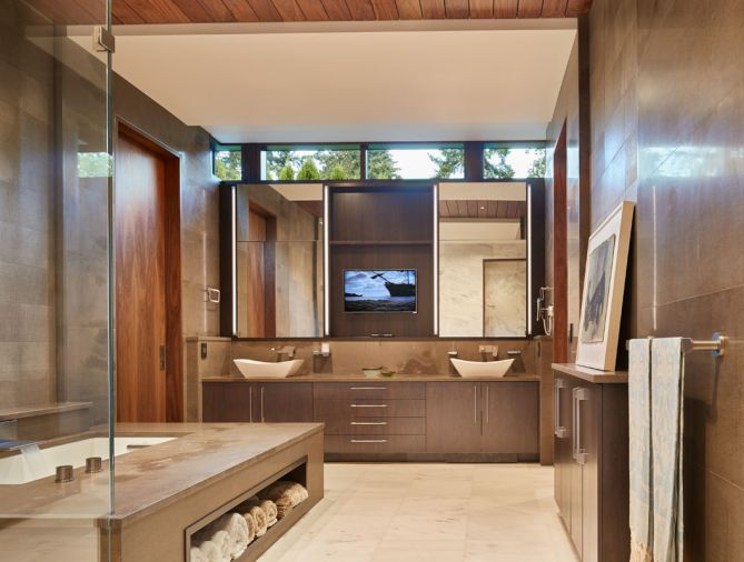 Designed to evoke a spa-like setting, the master bath boasts heated floors and tub deck, an extra-deep tub, and a hidden television set behind one of the vanity mirrors. The walls and tub surround are grey Fusano limestone, which has a lovely buttery texture. The cabinets are built from walnut.