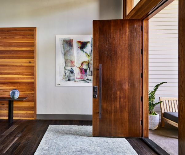 "Collin wanted the first ""handshake"" of the home to be the hand-hewn handle on the Alder door. A warm cedar wall bumps up against the darker prefinished Siberian Oak Provenza flooring."