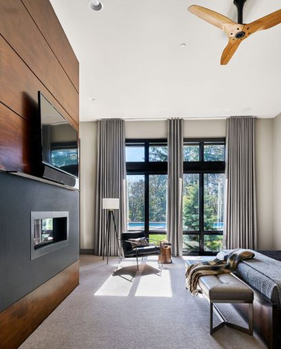 The relaxing master bedroom gets a simple set of window treatments; alder wood backed television with blued steel fireplace surround. Big Ass Haiku fan plays off Paul Schatz lamp, wooden stump side table, leather chair and bench.