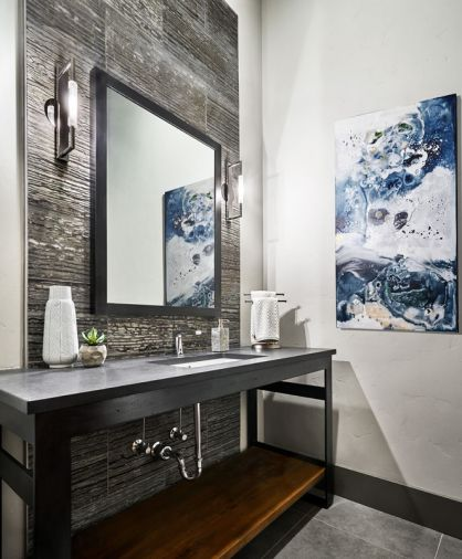 The powder room located off the entry features an industrial steel table, Caeserstone quartz countertop and a marble zebra vein wall tile, with contrasting polished nickel Decor Walther sconces.