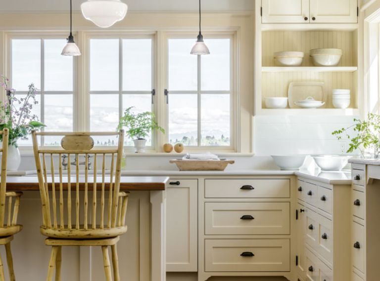 The traditional farmhouse kitchen is built around custom cabinetry from Warmington & North, a Seattle-based cabinetry specialist. Warm neutral tones on the walls, cabinets, area rug, and furniture enhance the glow that comes from wrap-around windows.