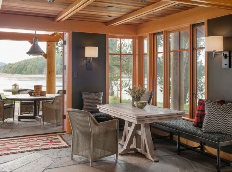 This cabin on the shores of San Juan Island invites the outdoors in at every turn. The same variegated blue stone used for the patio also forms the floor of the main entry room, creating a sense of continuity and cohesion. A built-in bench around two sides of the dining table keeps the small space streamlined, while the bank of windows in the corner provides an immediate connection to the shoreline just outside.