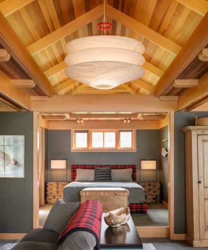 A light fixture from Ingo Maurer channels a Japanese design sensibility, while that classic Filson plaid makes another appearance on the bed's headboard and box spring surround. Careful symmetry gives the interior a calm, harmonious feel.