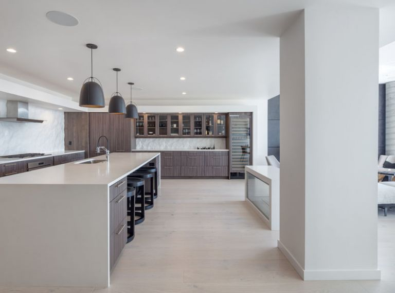 """Anytime you are dealing with an open plan,"" says interior designer Kricken Yaker, ""it's tricky to design."" She balanced the masculine elements, with textures that softened the space. Steelhead Architecture's L-Shape kitchen design enhances the flow."