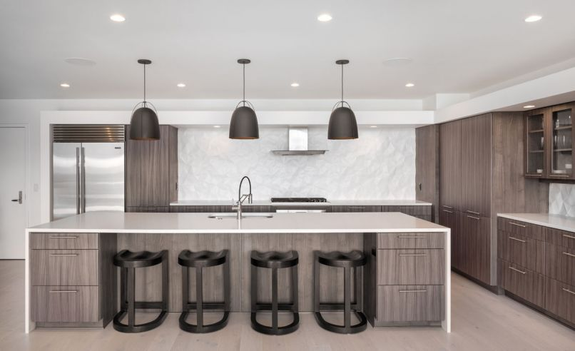 Veneer-clad cabinets and Haleigh Wire Dome Rod pendants from Rejuvenation contrast with the 3-D backsplash by Modular Arts.
