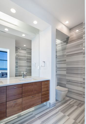 Linear marble tiling from Oregon Tile and Marble gives the bathroom its eye-catching graphic design.