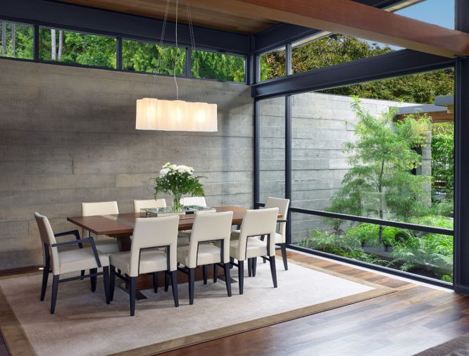 Board form concrete walls bring a warm industrial vibe to the dining room, while floor-to-ceiling windows introduce lush outdoor views. By designing the structure as well as the landscape, McClellan Architects ensures that everything works together.