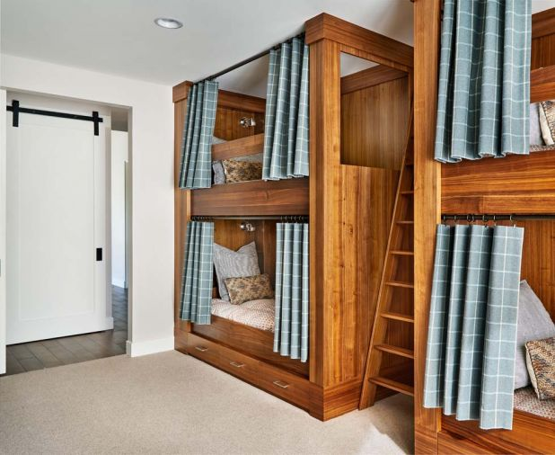 Curtains enable children to get better rest; LED lights make easy reading; plug-ins charge electronics. Bottom bunks feature storage. Laundry behind sliding barn door.