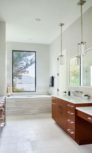 The subtle master bathroom design scheme draws the eye out toward the beautiful view of the lake and the mountains. Vein cut limestone from Intrepid Marble and Granite provides softness and depth to the large soaking tub surround.