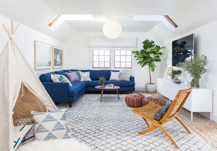 "An upstairs den was transformed from a dark nook to a light, bright space that serves double-duty as a kid's playroom during the day and an adult retreat in the evening. ""During the day we can have it messy and crazy with toys, and then it's really easy to clean up,"" says the homeowner. ""Then at night, we'll sit up there, light a candle, and watch TV, and it feels like a totally adult space."""