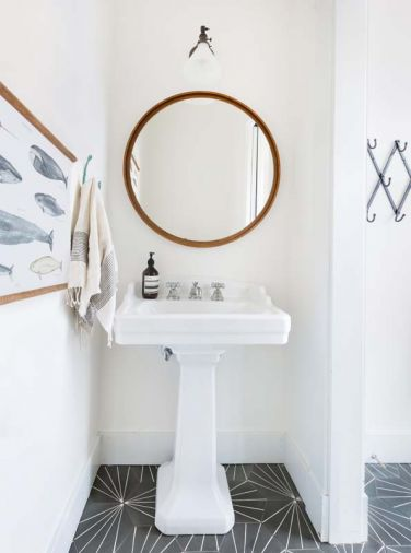 "The powder room off the kitchen features simple, crisp lines. ""I loved bringing the wood in with the mirror because it warms up all the white,"" says Heidi. Geometric tile is from Cement Tile Shop."