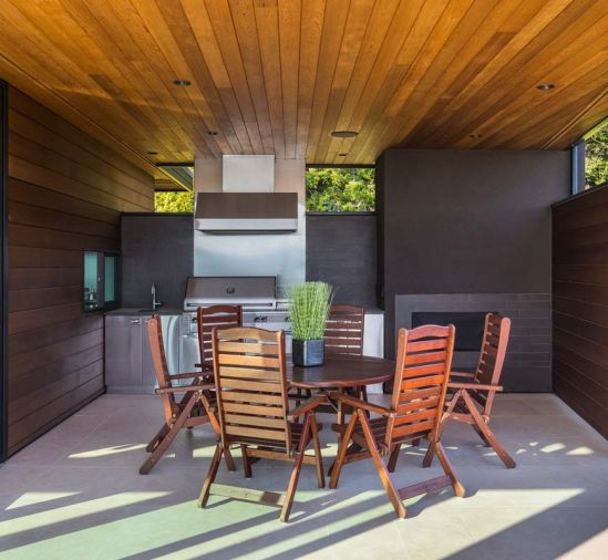 A pass through window connects the adjacent indoor kitchen with the covered outdoor one. Jensen Jarrah outdoor furniture warms the space.