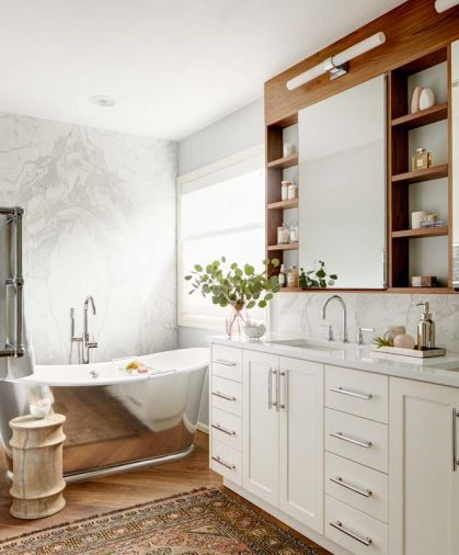 The bookmatched marble makes a stunning backdrop to the Waterworks tub. Robern medicine cabinets bordered by walnut perimeter,
