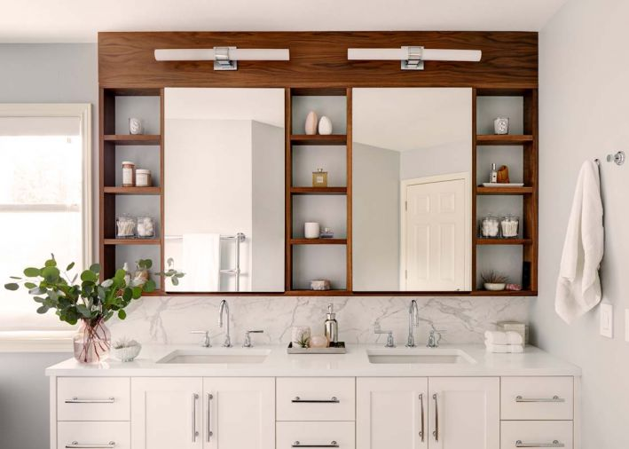 Wall-to-wall for generous storage, with marble wrapped within it. Sinks from Kohler. Vanity sconces by Waterworks.