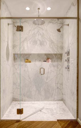 The bookmatched marble echoed in the shower, the shampoo niche extends the entire width of the shower.