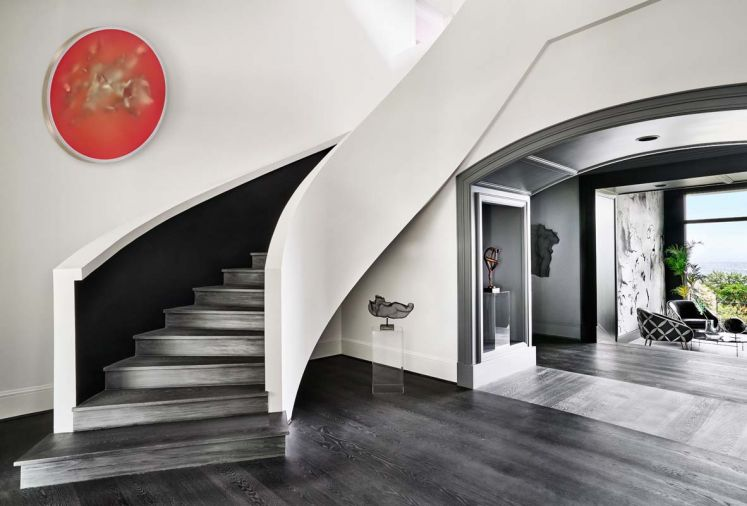 The original drywall staircase that had a wooden railing became all drywall; stair treads are engineered wood from Castle Bespoke Flooring; LED strip lighting lights black staircase wall. Peter Gronquist painting hovers like the moon.
