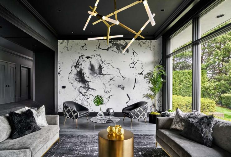 Touches of gold add bling to the dramatic black, gray and white color scheme found in the living room – from the graduated circular DWR coffee tables to the angular Agnes Chandelier. The outside comes in with a potted palm crowned in chartreuse moss, a mound of limes and a faux leaf sprouting from a glass vase.