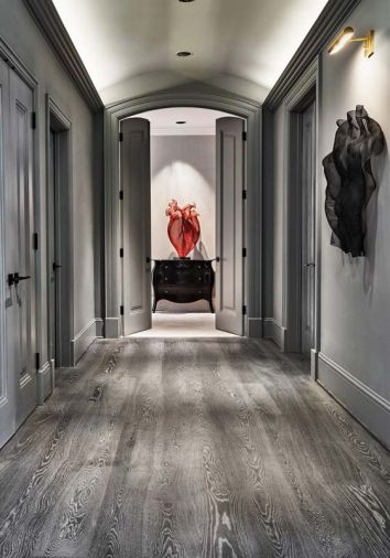 By unifying the hallway finishes that included wood and painted surfaces with a single gray paint, Boyer's red steel mesh artwork becomes center stage.