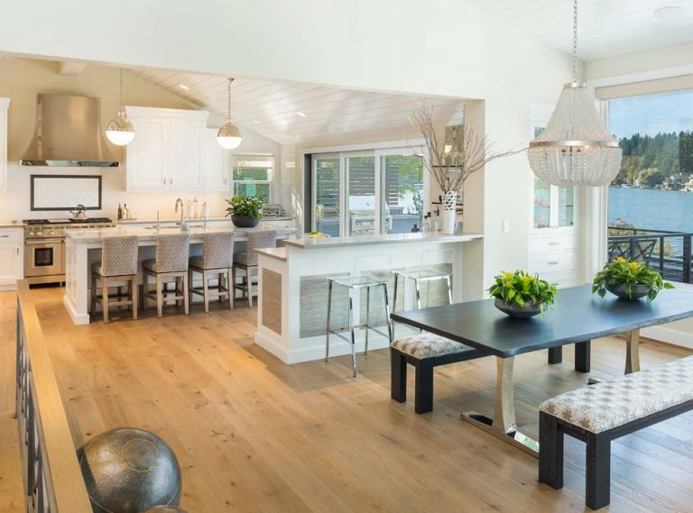A reflective white lap siding ceiling brings light into kitchen. Phillip Jeffries grass cloth panels add panache to the bar. Curry & Co. French Empire crystal chandelier brings shine to Vanillawood sourced table; Kravet upholstered benches.