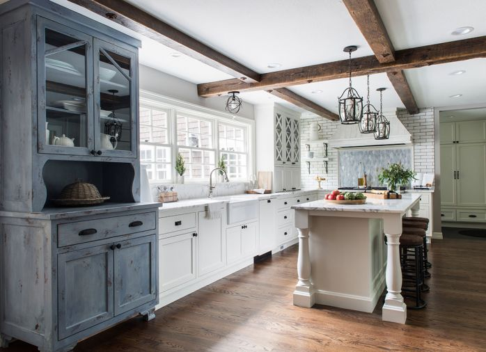 "To underscore the home's established farmhouse style, Taryn designed a rustic hutch to bring a warmer, more traditional feel into the kitchen. Countertops and backsplash are Calacatta Vettogli marble sourced from Intrepid Marble & Granite. ""Throwing in a lot of texture was important,"" says Taryn. ""In the kitchen alone, you have this really cool Ann Sacks white brick behind the range, the distressed wood hood, the hutch, and the backsplash, which is a beautiful glass mosaic."""