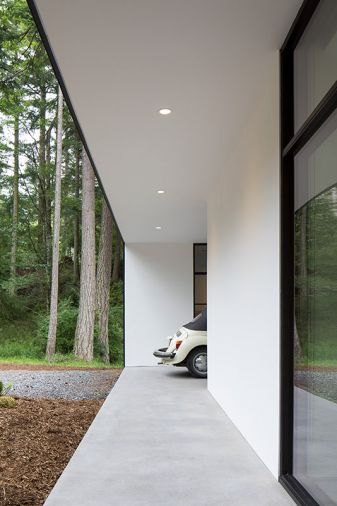 Outside, looking towards the carport, wide eaves create shelter from the rain while minimizing glare inside the home.