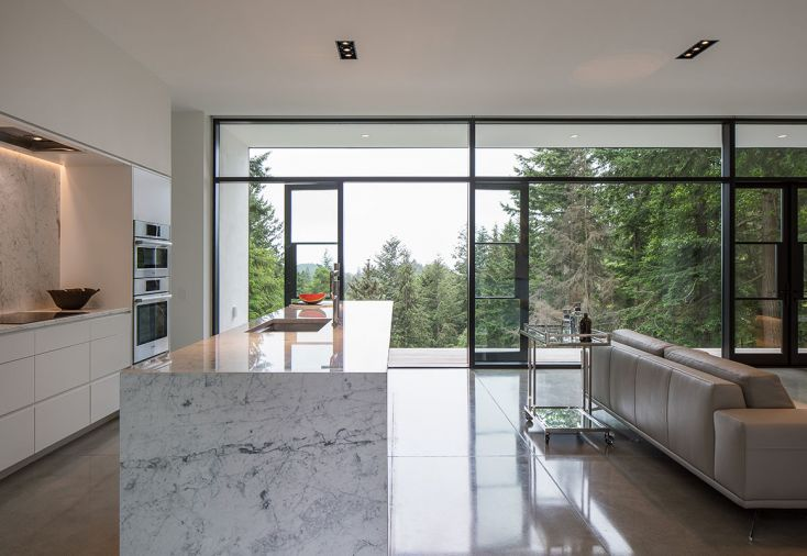 In the kitchen, the island is fully wrapped with with statuary marble, a material chosen for its luster and texture as well as its ability to combine the two primary colors in the home, white and gray.