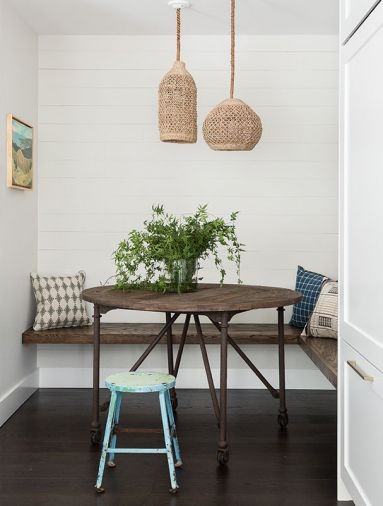 A built-in breakfast nook serves double-duty as an afternoon homework station. Cushion-free benches are easy to clean and maintain. Tight shiplap on the wall at the back of the nook gives the area a rustic feel, underscored by a vintage stool.