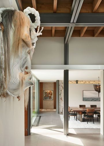 A giant indigenous art mask graces the great room, residing over structural exposed blackened steel and wood beams that look toward the dining room and entry hallway.
