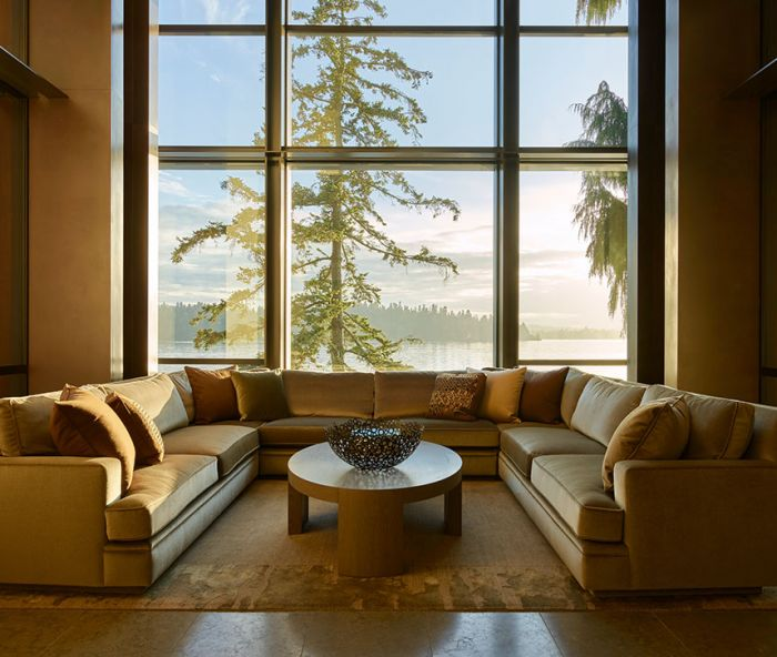 Hunziker's U-shaped Coraggio mohair sofa nestles before stately Fleetwood windows facing lake on Lapchi rug.