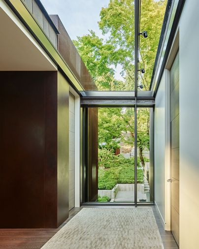 Baba designed the first-floor landing window to overlook entry and sloped property then lit it above from skylight. Cor-Ten steel column left adds rustic texture; Lapchi rug.
