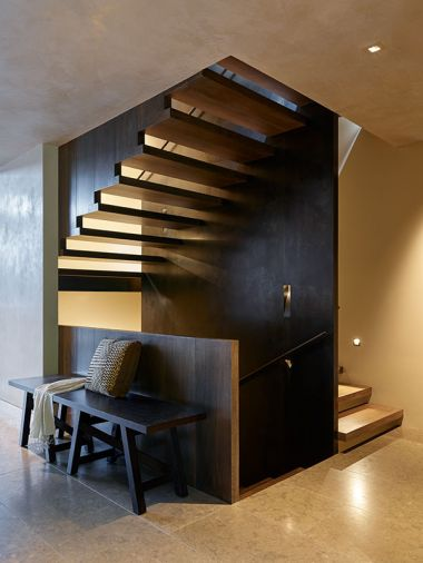 Staircase with bench and pony wall descends from the living/dining level to lower level and rises to the first landing, childrens' bedrooms and bath.