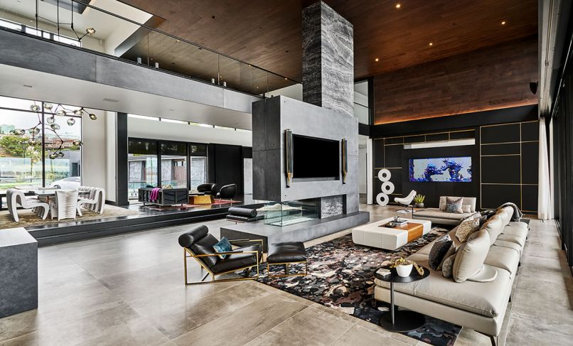 A fireplace cantilevers dramatically off a structural marble pillar and concrete base. Roche Bobois Scenario sectional. Holly Hunt Oasis Cocktail Ottoman.