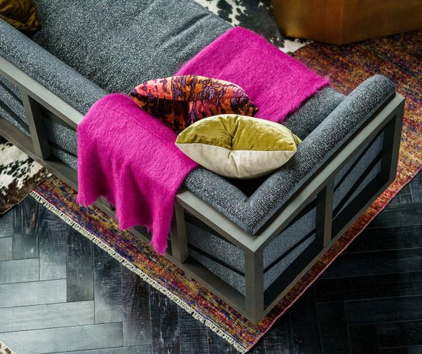 A hot pink throw pops against custom fabric on an Arteriors sofa.
