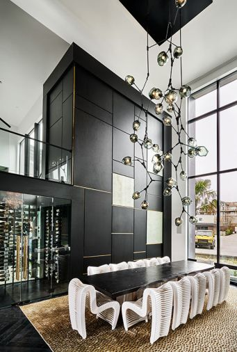 Collaboratively-designed 19' black metal and blown glass chandelier by Keir Legree of Savoy Studios. White Seatbelt dining chairs and Live Edge dining table by Phillips Collection. West Coast Wine Cellars glass-enclosed, temperature-controlled wine cellar stores up to 400 bottles. Feizy custom rug.