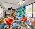 "Bright blue-impregnated Provenza bowling alley flooring sets the scene for futuristic Roche Bobois orange swivel chairs, cocktail mirrored table by Phillips Collection and hand knotted rug by Kush—all teaming with ""rad"" Alec Monopoly graffiti mural."
