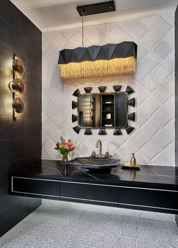 A Mirror Image black leather and brass mirror sparkles amidst the black and white themed powder room. The sculptural light fixture by Arteriors softens the geometric elements found in the Kelly Wearstler flooring and tile wall by Ann Sacks.